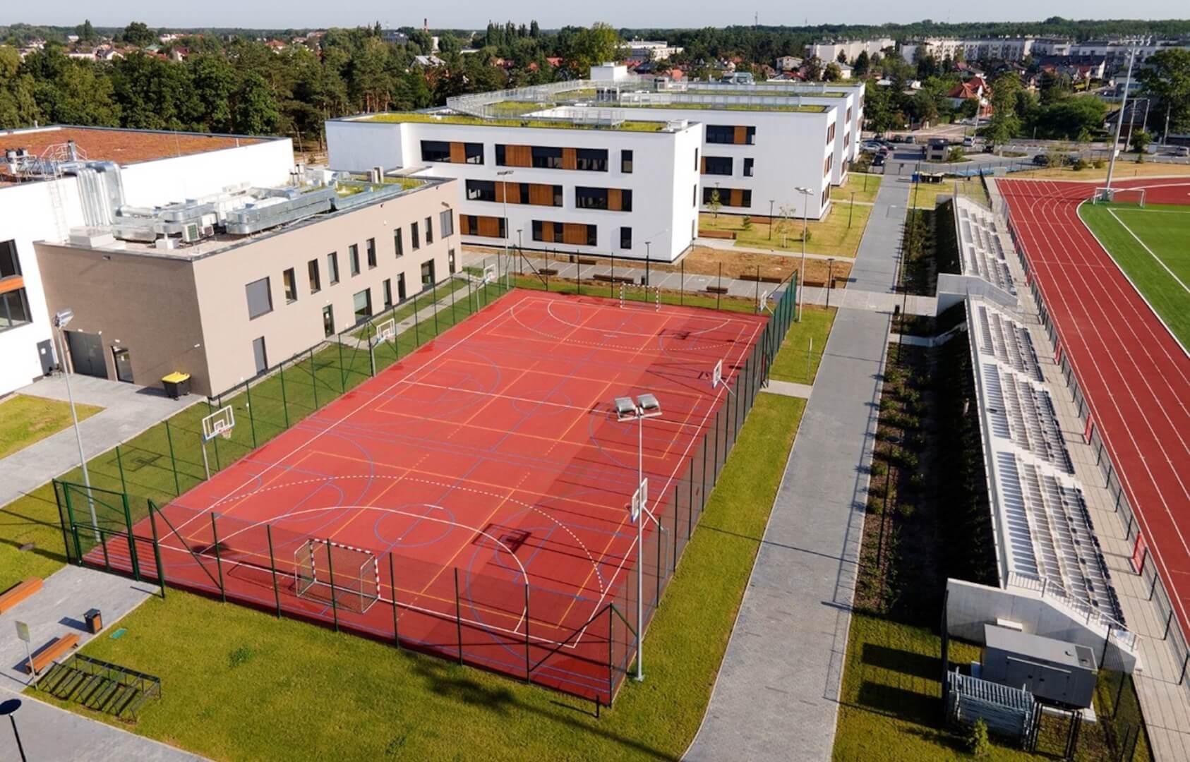 Widok z lotu ptaka na boisko do gier zespołowych i trybuny stadionu piłkarskiego na tyłach budynku B