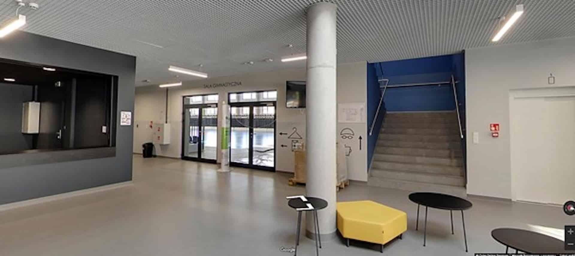 Widok z korytarza na wejście do hali sportowej i schody prowadzące na piętro, gdzie jest basen i sala widowiskowa